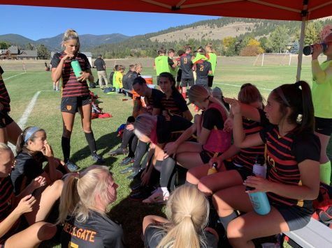 The soccer team huddles on the sideline to talk during halftime of their game against Glacier High School on Oct. 2. Their cleats are laced with teal and purple ribbons in solidarity with the Glacier soccer teams.